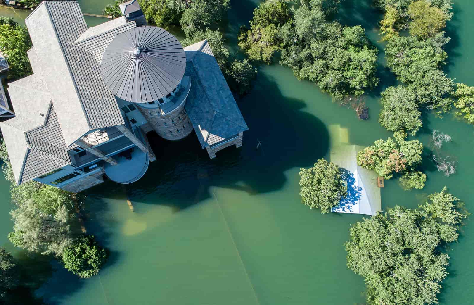 Straight down above flooded Mansion home and Luxury house under the flood waters , rising water level along the Colorado River forces evacuations and natural disaster declaration of Austin and Central Texas